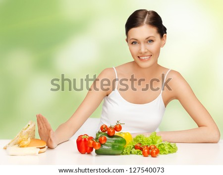 picture of beautiful woman with hamburger and vegetables - stock photo