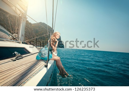 picture of beautiful young woman sitting on the yacht - stock photo
