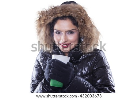 Picture of beautiful young woman wearing winter jacket and holds hot coffee in the studio, isolated on white background - stock photo