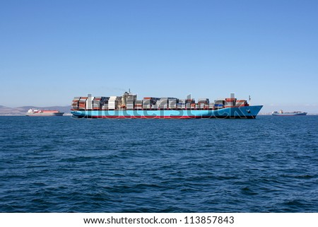 Picture of blue sea with a container ship driving along the horizon - stock photo