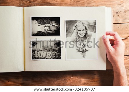 Picture of bride and groom in photo album. Studio shot on wooden background. - stock photo