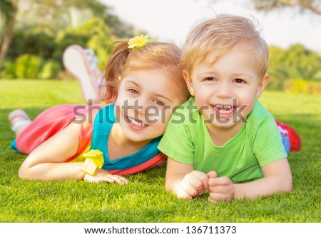 Picture of brother and sister having fun in the park, two cheerful children laying down on green grass, little girl and boy playing outdoors, best friends, happy family, love and happiness concept - stock photo