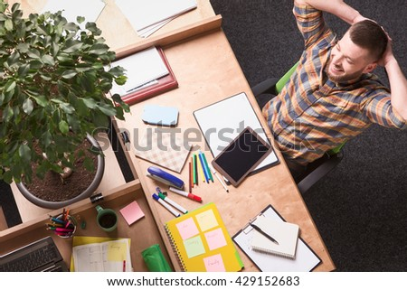 Picture of businessman having rest and relax while working in office. Handsome man sitting at table in front of his laptop computer. - stock photo