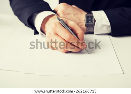 picture of businessman writing something on the paper - stock photo