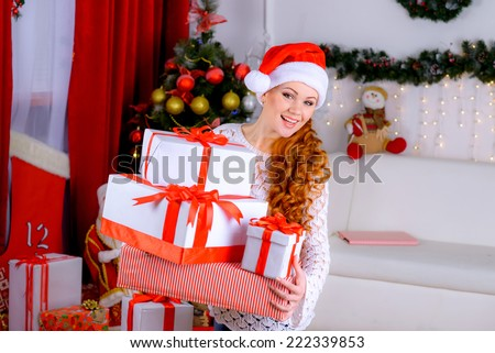 picture of cheerful santa helper girl with gift box near the Christmas tree - stock photo