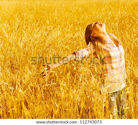 Picture of cheerful teenager having fun in countryside, cute happy female standing on wheat field with raised open hands and looking up, blond girl enjoying autumn nature, fall season - stock photo