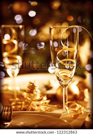 Picture of Christmas table setting, retro style photo, glasses for champagne, golden Christmastime decorations, white festive dishware, soft focus, New Year dinner, xmas eve, luxury home interior - stock photo
