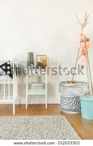 Picture of crib and small table with infant accessories - stock photo