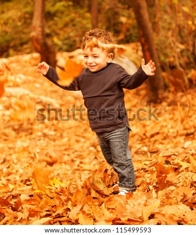 Picture of cute little boy run with raised up hands in autumnal woods, pretty small male walking in the park, cheerful infant having fun in fall forest, adorable toddler play game on backyard - stock photo