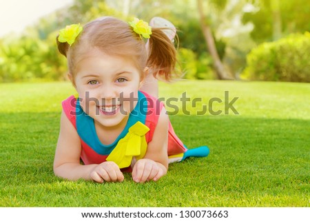 Picture of cute little girl lying down on green grass in park, cheerful child resting on the field on backyard, pretty kid having fun outdoors in springtime, spring nature, sunny day, happy childhood - stock photo
