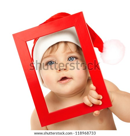 Picture of cute toddler looking through red Christmas frame isolated on white background, closeup portrait of adorable kid with blue eyes wearing funny Santa Claus hat, New Year holiday - stock photo