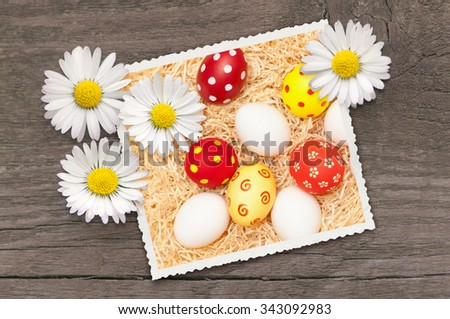 Picture of Easter eggs decorated with daisies on wooden board; Easter holiday greetings - stock photo