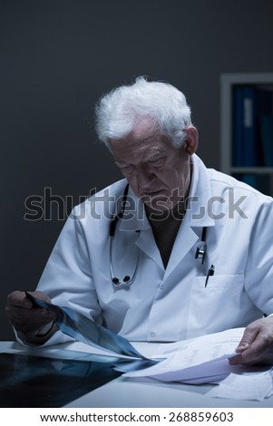 Picture of elder physician analyzing clinical case - stock photo