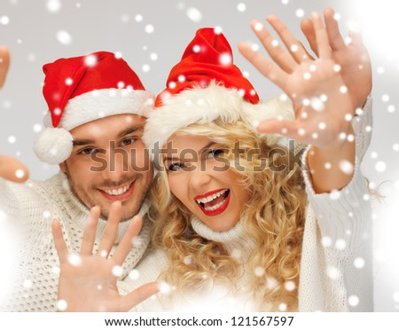 picture of family couple in sweaters and santa's hats - stock photo