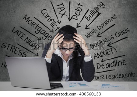 Picture of female Indian entrepreneur with a laptop and financial charts on the table, looks stressful thinks her problems - stock photo