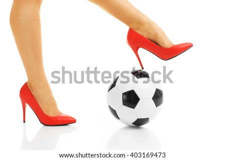 Picture of female legs in red heels and football - stock photo