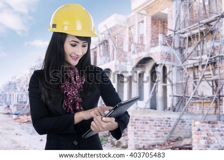 Picture of female real estate agent using digital tablet on the residential construction - stock photo