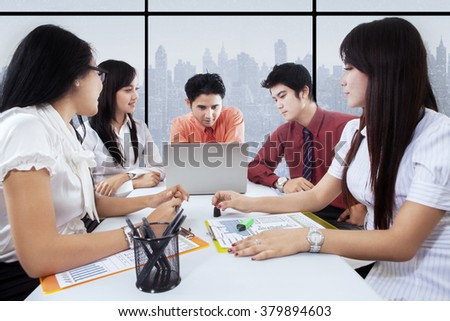Picture of five young entrepreneurs discussing in the office with laptop computer and documents - stock photo