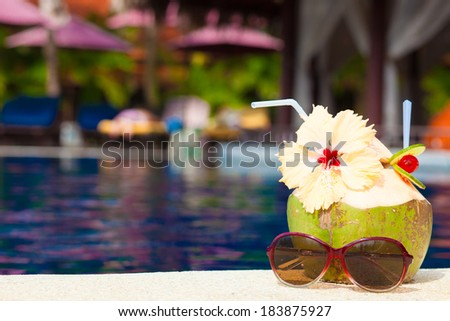 picture of fresh coconut cocktail and pink sunglasses near luxury pool - stock photo