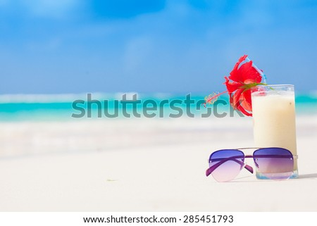 picture of fresh pina colada and sunglasses on tropical beach - stock photo