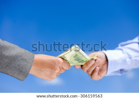 Picture of hands giving and receiving dollar bills. Side view in horizontal format over a blue sky sunny outdoors background. - stock photo