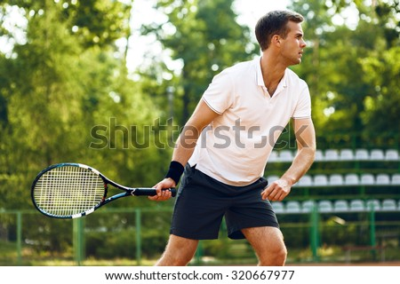 Picture of handsome young man on tennis court. Man playing tennis. Man hitting tennis ball. Beautiful forest area as background - stock photo