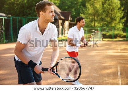 Picture of handsome young men on tennis court. Men playing tennis. Man is ready to hit tennis ball. Beautiful forest area as background - stock photo
