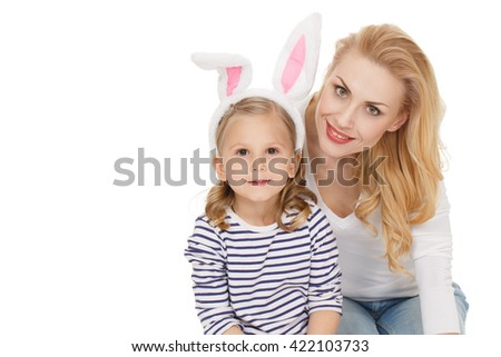 Picture of happiness. Shot of adorable mature mother and her daughter wearing bunny ears looking to the camera cheerfully isolated on white. - stock photo