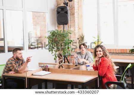 Picture of happy and cheerful business people looking at camera while working in office. Corporate freelancers discussing new business projects. - stock photo