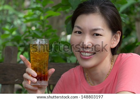 picture of happy and smiling asian woman with glass of cola - stock photo