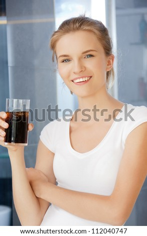 picture of happy and smiling teenage girl with glass of cola - stock photo
