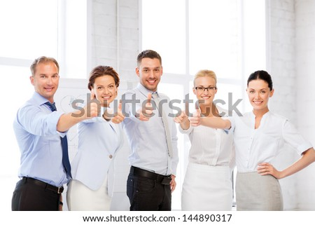 picture of happy business team showing thumbs up in office - stock photo