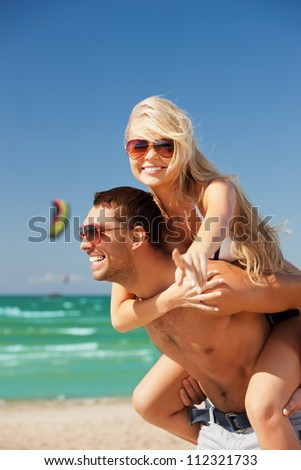 picture of happy couple in sunglasses on the beach. (focus on woman) - stock photo