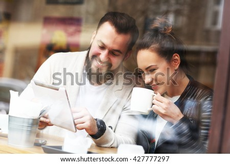 Picture of happy couple using tablet in restaurant - stock photo
