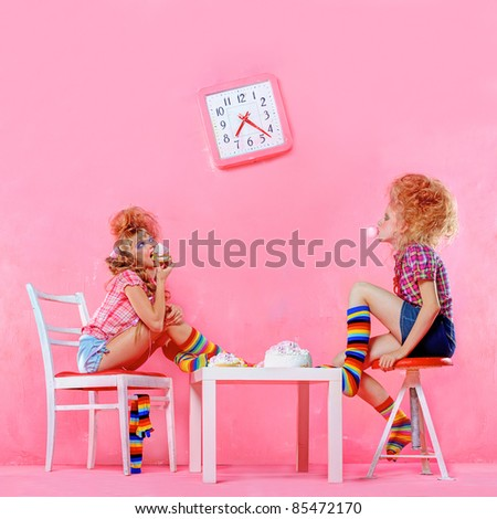 Picture of happy girsl eating cake isolated on pink interior - stock photo