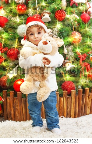 Picture of happy small boy holding teddy bear in hands on beautiful decorated Christmas tree background, little child wearing red Santa Claus hat, New Year celebration, child's xmas party - stock photo