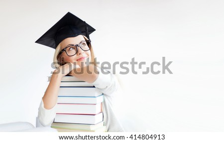 picture of happy student in graduation cap with stack of books - stock photo