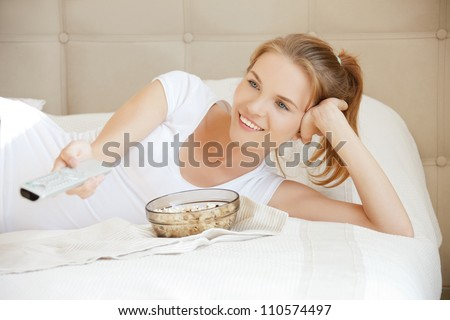 picture of happy teenage girl with TV remote and popcorn - stock photo