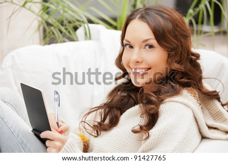 picture of happy woman with small notepad - stock photo