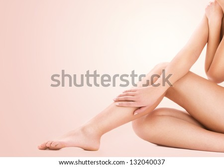 picture of healthy naked woman legs over beige background - stock photo