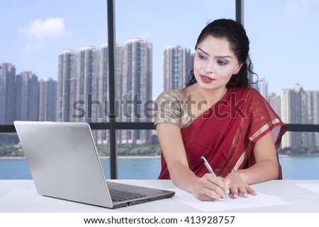 Picture of Indian young businesswoman working in the office while wearing sari clothes and using laptop - stock photo