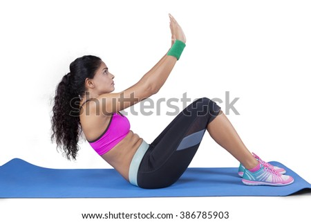 Picture of indian young woman doing sit up - stock photo