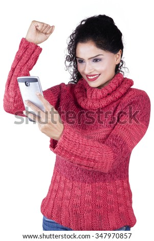 Picture of joyful indian woman wearing sweater in the studio while reading message on the cellphone and raise hand - stock photo