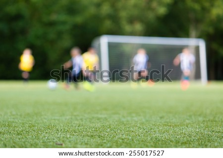 Picture of kids soccer training match with shallow depth of field. Focus on foreground. - stock photo