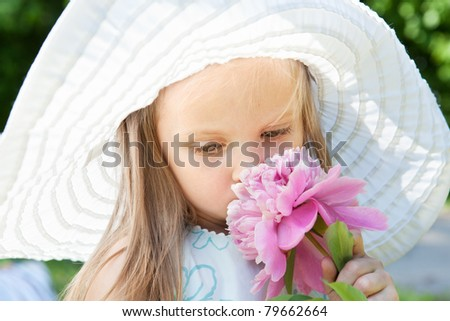 Picture of little blonde girl smelling a pink flower - stock photo