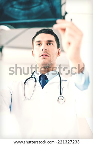picture of male doctor or dentist looking at x-ray - stock photo