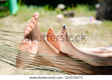 Picture of man and child barefoot with green antiseptic on child's foot. Closeup of happy family lying on hammock on sunny summer day countryside background. - stock photo