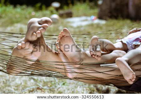 Picture of man and children legs barefoot. Closeup of happy family lying on hammock on sunny countryside background. - stock photo