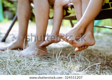Picture of man and children legs barefoot. Closeup of happy family sitting on garden swing on sunny countryside background. - stock photo