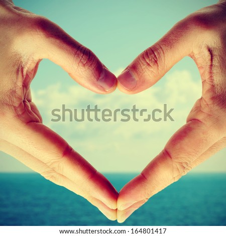 picture of man hands forming a heart with the sea and the sky in the background, with a retro effect - stock photo